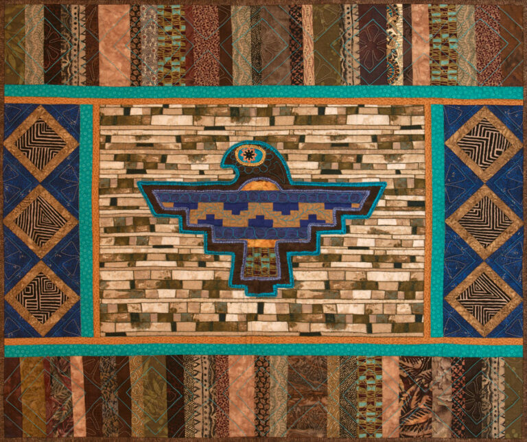 This quilt features an appliqued Thunderbird with a Seminole pieced panel inset, embellished with hand embroidery.